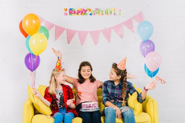 Grupa dziewczyny siedzi na kanapie z urodzinowym tortem