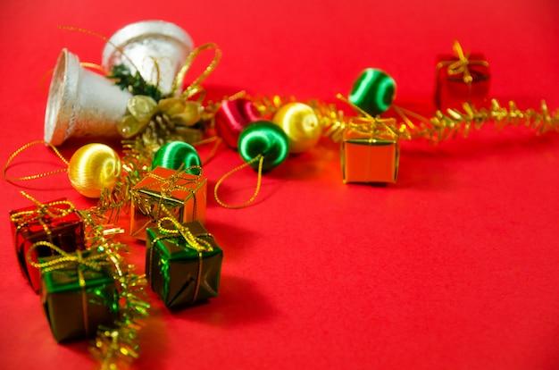 Grupa dzwon, piłka i prezent w bożych narodzeniach na czerwonym tle na odgórnym widoku