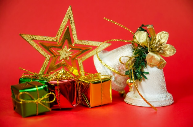 Grupa dzwon, prezent i gwiazda w bożych narodzeniach na czerwonym tle