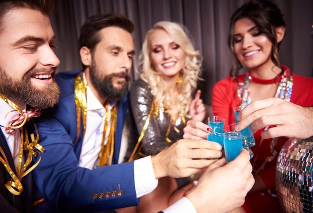 Grupa eleganckich ludzi z opiekaniem blue curacao