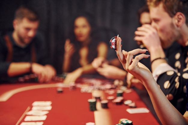 Grupa eleganckich młodych ludzi grających razem w pokera w kasynie