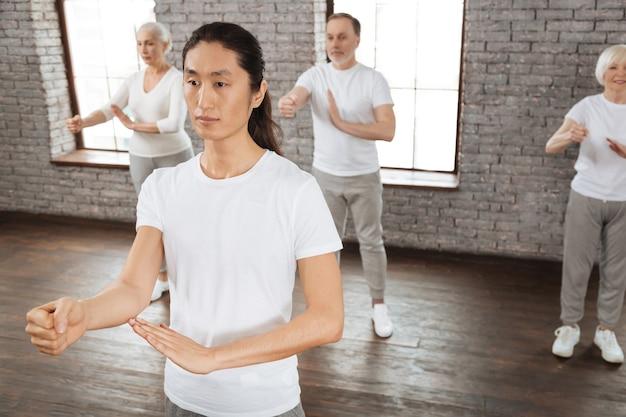 Grupa emerytów wykonująca jogi z wyprostowanymi plecami, stojąc za swoim nauczycielem