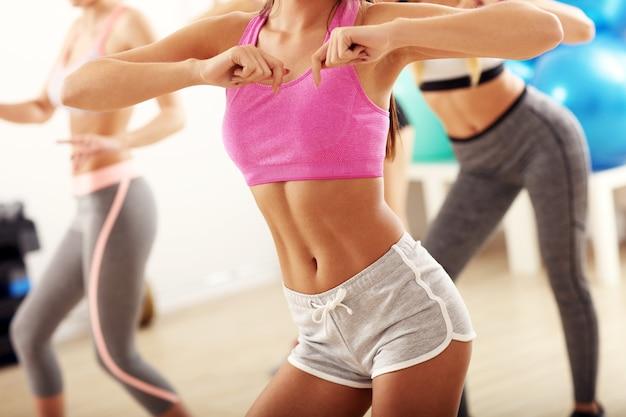 Grupa energicznych ludzi z trenerem tańczącym na siłowni