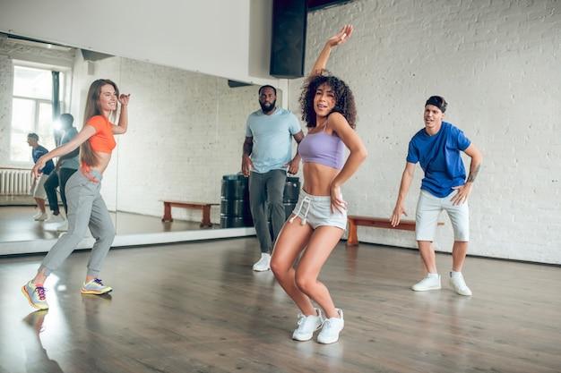Grupa energicznych młodych ludzi w sportowej odzieży i trampkach zaangażowanych w taniec