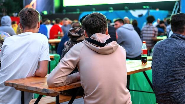 Grupa facetów siedzących przy stole i oglądających piłkę nożną w miejscu publicznym