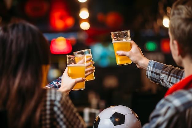 Grupa fanów piłki nożnej przy piwie świętuje zwycięstwo ulubionej drużyny w barze sportowym. transmisje telewizyjne, młodzi przyjaciele odpoczywają w pubie
