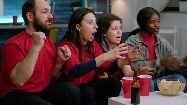 Grupa fanów sportu rasy mieszanej oglądając mecz piłki nożnej w telewizji, siedząc na kanapie późno w nocy w salonie. wieloetniczni przyjaciele zawiedzeni po przegranej drużynie w grze