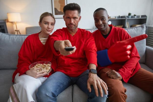Grupa fanów sportu ubranych na czerwono podczas oglądania meczu w domu i siedzących na kanapie