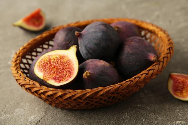 Grupa fig w drewnianej misce na szarym tle. zdjęcie pionowe.