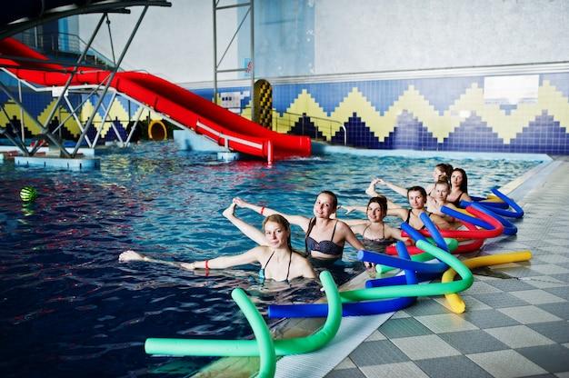 Grupa fitness dziewcząt robi ćwiczenia aerobowe w basenie w parku wodnym.