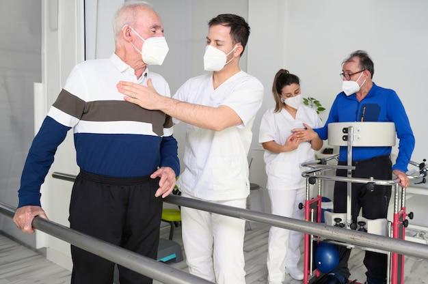 Grupa fizjoterapeutów pracujących w ośrodku odwykowym, pomagająca pacjentom.