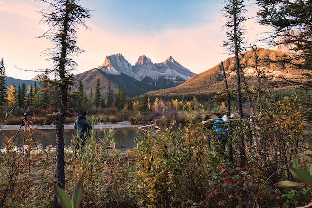 Grupa Fotografów Robiących Zdjęcie W Three Sisters Mountains To Skaliste Góry W Jesiennym Lesie W Canmore, Park Narodowy Banff, Kanada Premium Zdjęcia