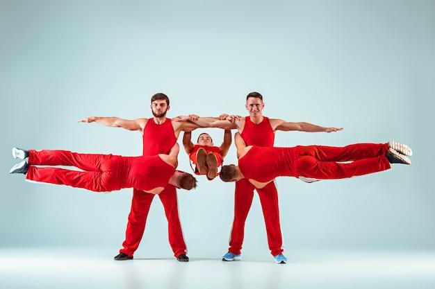 Grupa gimnastycznych akrobatycznych mężczyzn rasy kaukaskiej w równowadze stanowi