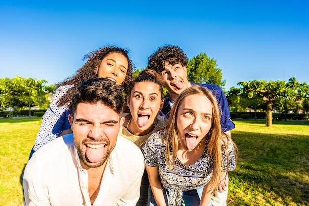 Grupa głupich, młodych, wielorasowych, milenialsów, którzy robią śmieszne miny z językiem, otwartymi ustami i przymrużonymi oczami pozują do portretu w parku miejskim. żyj lekko, bawiąc się na łonie natury