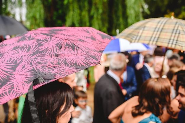 Grupa gości na uroczystości chroniąc się przed deszczem z parasolem.