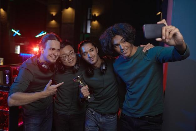 Grupa graczy pozuje do kamery telefonu komórkowego z trofeum po konkursie