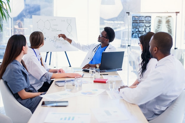 Grupa ilnternatiomal lekarzy lub stażystów ze spotkaniem mentora i notatek w sali szpitalnej.