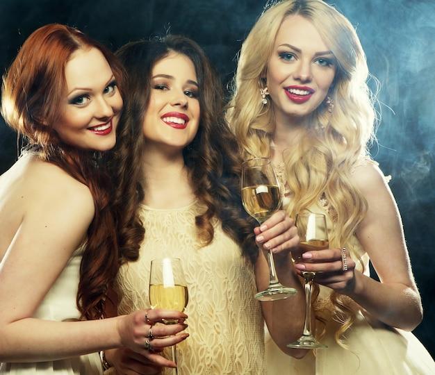 Grupa imprezujących dziewcząt brzęczących fletami z winem musującym