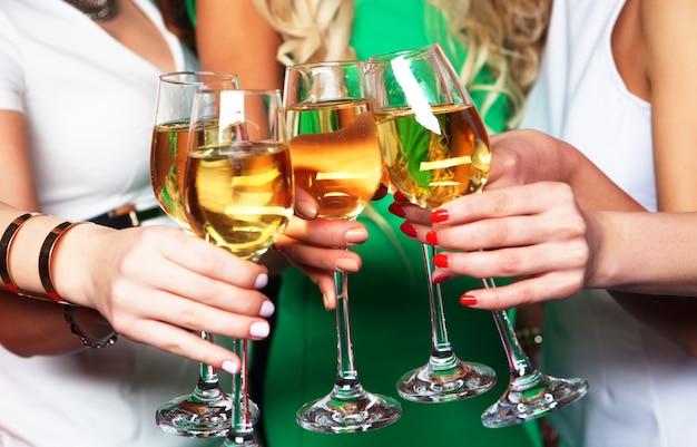 Grupa imprezujących dziewczyn szczękających fletów z winem musującym