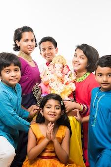 Grupa indyjskich dzieci posiadających ganpati idol na festiwalu ganesh lub chaturthi, powitanie boga. stojąc na białym tle na białym tle