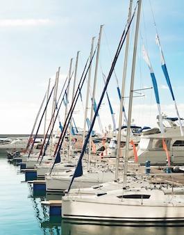 Grupa jachtów żaglowych do regat sportowych zakotwiczonych w porcie morskim