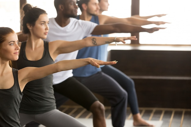 Grupa jogin ludzi w warrior two pose