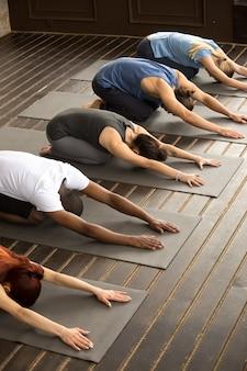 Grupa jogów ludzie w balasana pozie