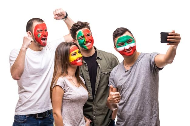 Grupa kibiców kibiców drużyn narodowych pomalowana flagą portugalii, hiszpanii, maroka, iranu robi selfie z telefonu. emocje fanów.