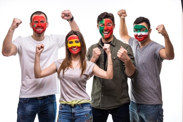 Grupa kibiców kibiców drużyn narodowych z pomalowaną flagą portugalii, hiszpanii, maroka, iranu radośnie krzyczy do kamery. emocje fanów.