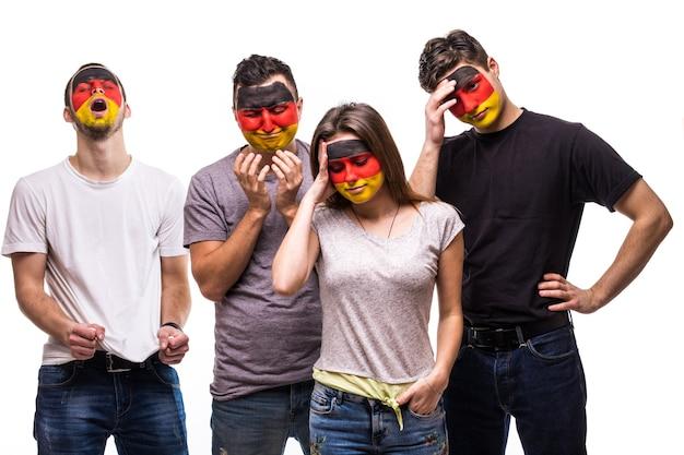 Grupa kibiców kibiców reprezentacji niemiec z namalowaną flagą mierzy się ze smutnymi, sfrustrowanymi emocjami. emocje fanów.