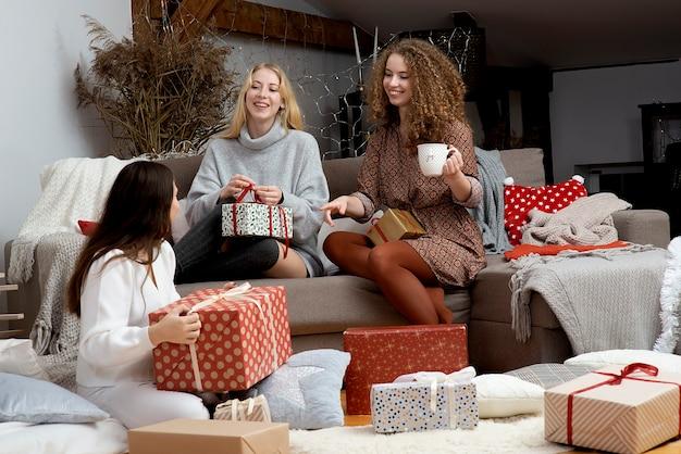 Grupa kobiet bawiących się pakowaniem prezentów w domu, wspaniała praca zespołowa przyjaciół pakujących prezenty na święta bożego narodzenia