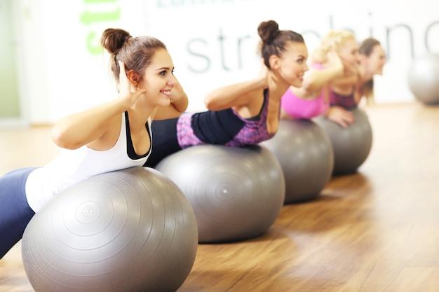 Grupa kobiet ćwiczących na piłkach w siłowni