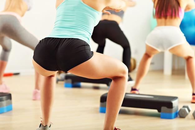 Grupa kobiet ćwiczących na siłowni wykonujących przysiady