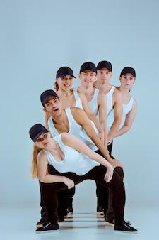 Grupa kobiet i mężczyzn tańczących choreografię hip-hopową