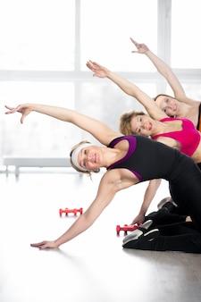 Grupa kobiet robi fitness ćwiczenia w klasie