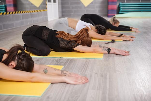 Grupa kobiet robi pozę dziecka na zajęciach jogi
