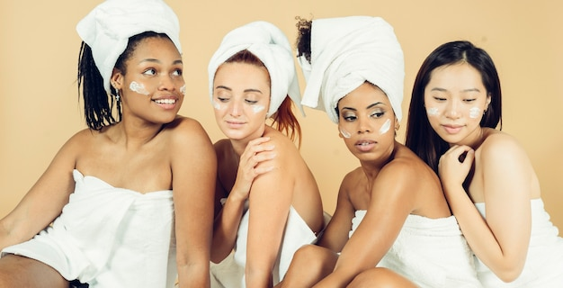 Grupa kobiet różnych ras jest poddawana zabiegom kosmetycznym na żółtym tle