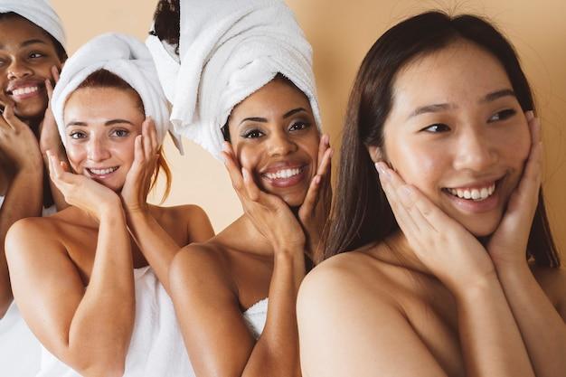 Grupa kobiet różnych ras stoi w rzędzie, dotykając się nawzajem szczęśliwymi twarzami