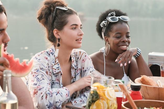 Grupa kobiet siedzi przy stole, pije sok i uśmiecha się na zewnątrz