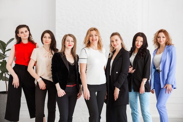 Grupa kobiet ubranych w styl biznesowy pozowanie i patrząc w kamerę.