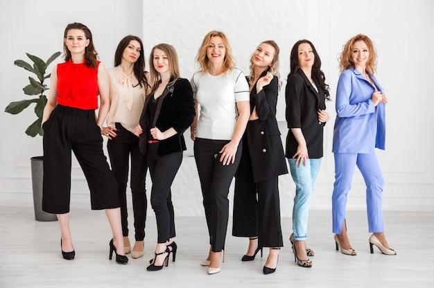 Grupa kobiet ubranych w styl biznesowy stoją razem i pozują do kamery.