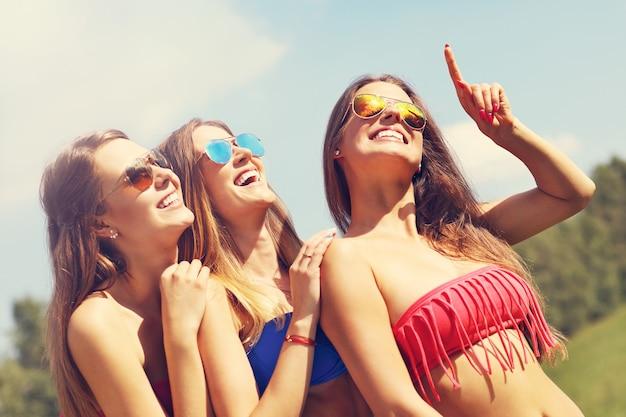 Grupa kobiet w bikini pokazująca coś na zewnątrz