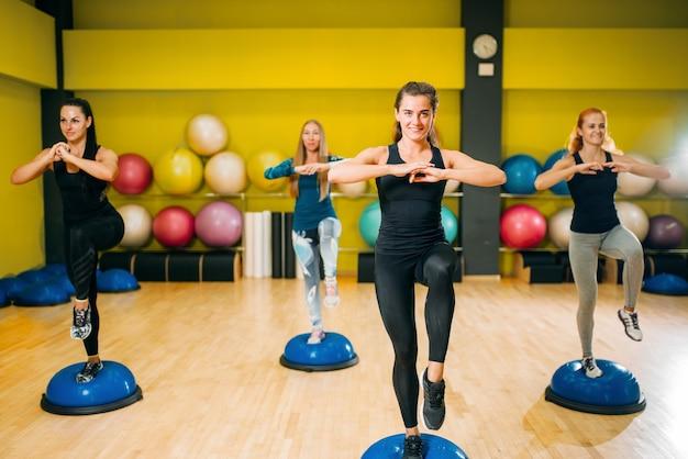 Grupa kobiet w odzieży sportowej, ćwicząc na treningu fitness. pracy zespołowej kobiecego sportu w siłowni.