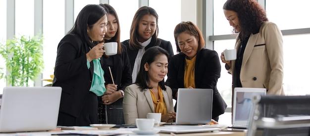 Grupa kobiet w średnim wieku businesswoman w dorywczo biznesu nosi stojący uśmiechnięty picia kawy patrząc na kolegę, który wpisuje informacje biznesowe w komputerze przenośnym na stole konferencyjnym w biurze.