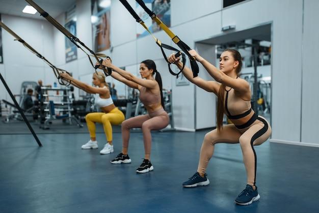 Grupa kobiet wykonujących ćwiczenia w siłowni, widok z tyłu