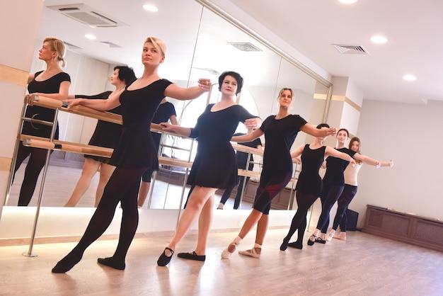 Grupa kobiet wykonuje ćwiczenia baletowe, podnosząc ręce do góry za pomocą drążka na siłowni
