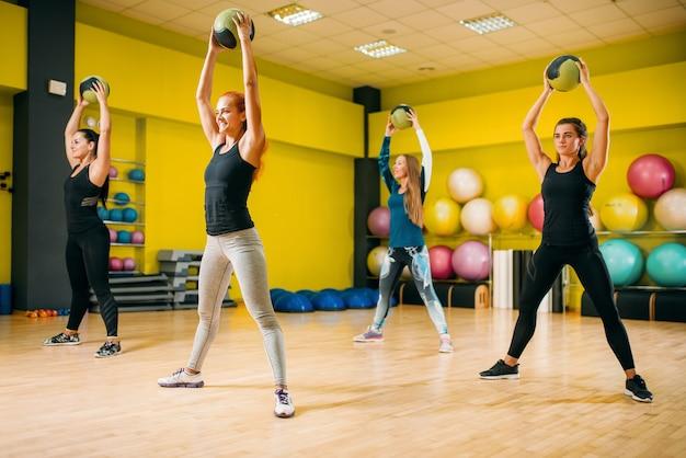 Grupa kobiet z kulkami na trening fitness. pracy zespołowej kobiecego sportu w siłowni. ćwiczenia fit, aerobik