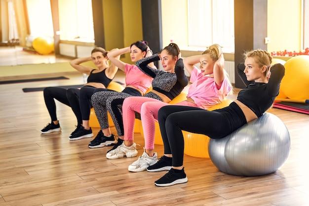 Grupa kobieta robi ćwiczenia na piłce fitness