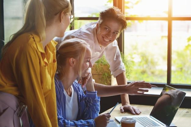 Grupa kolegów spotyka się w sali konferencyjnej podczas pracy nad dużą prezentacją