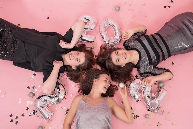 Grupa koleżanek bawi się na przyjęciu bożonarodzeniowym, leżąc na różowym tle z balonami z cyframi 2022, widok z góry.